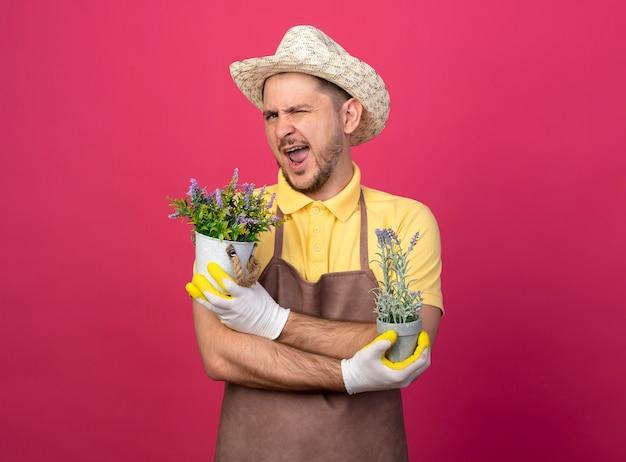 Jovem jardineiro vestindo macacão e chapéu em luvas de trabalho segurando vasos de plantas olhando para a frente sorrindo e piscando em pé sobre a parede rosa