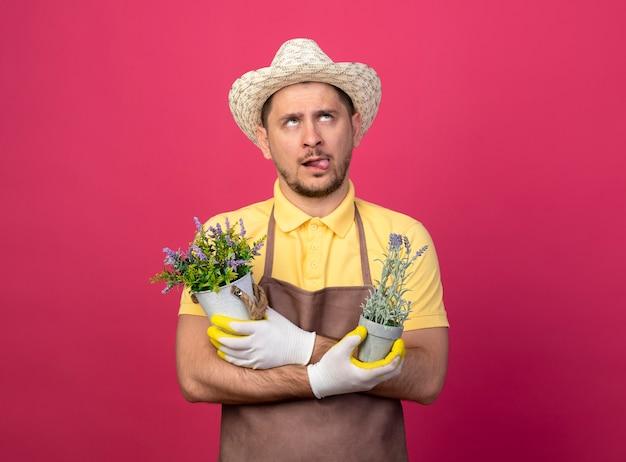 Jovem jardineiro vestindo macacão e chapéu em luvas de trabalho segurando vasos de plantas olhando para cima intrigado esticando a língua em pé sobre a parede rosa