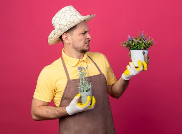 Jovem jardineiro vestindo macacão e chapéu em luvas de trabalho segurando vasos de plantas olhando para elas confusas e descontentes em pé sobre uma parede rosa