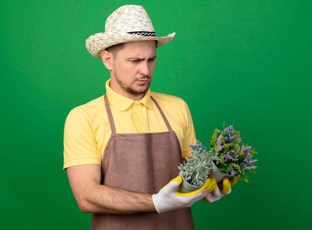 Jovem jardineiro vestindo macacão e chapéu em luvas de trabalho segurando vasos de plantas olhando para eles com cara séria em pé sobre a parede verde