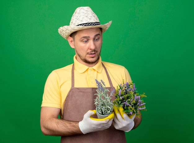 Jovem jardineiro vestindo macacão e chapéu em luvas de trabalho segurando vasos de plantas olhando para eles confusos em pé sobre a parede verde