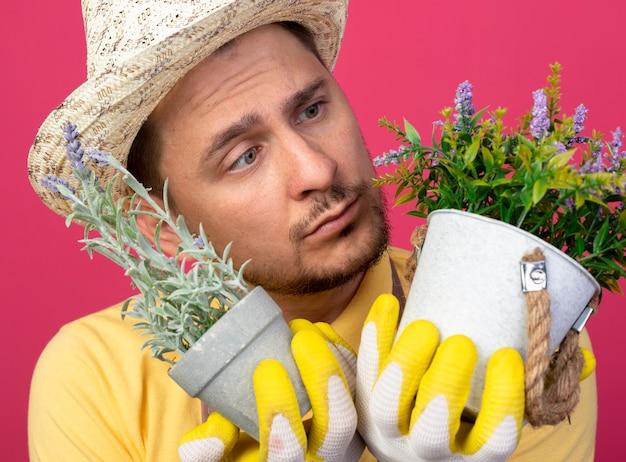 Jovem jardineiro vestindo macacão e chapéu em luvas de trabalho segurando vasos de plantas olhando para eles confusos em pé sobre uma parede rosa