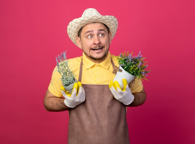 Jovem jardineiro vestindo macacão e chapéu em luvas de trabalho segurando vasos de plantas parecendo confuso