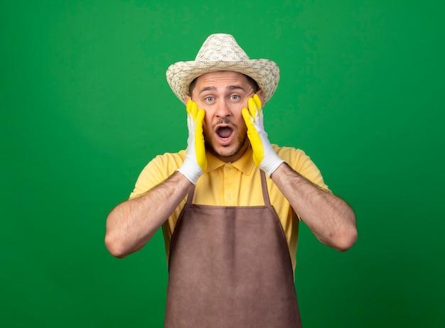 Jovem jardineiro vestindo macacão e chapéu em luvas de trabalho surpreso e surpreso com os braços no rosto