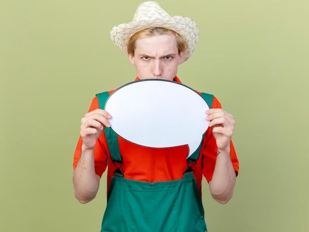 Jovem jardineiro vestindo macacão e chapéu mostrando sinal de bolha de discurso em branco looki para câmera com rosto sério franzindo a testa em pé sobre fundo claro