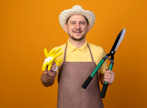 Jovem jardineiro vestindo macacão e chapéu segurando luvas de trabalho e corta-sebes com um sorriso no rosto