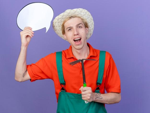 Jovem jardineiro vestindo macacão e chapéu segurando picareta e balão de fala