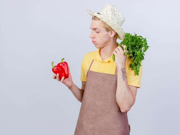 Jovem jardineiro vestindo macacão e chapéu segurando pimentão vermelho e ervas frescas, parecendo intrigado