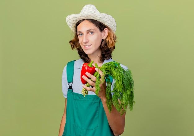 Jovem jardineiro vestindo macacão e chapéu segurando pimentão vermelho e ervas frescas