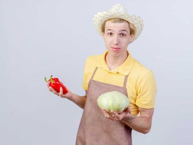 Jovem jardineiro vestindo macacão e chapéu segurando repolho e pimentão vermelho sorrindo