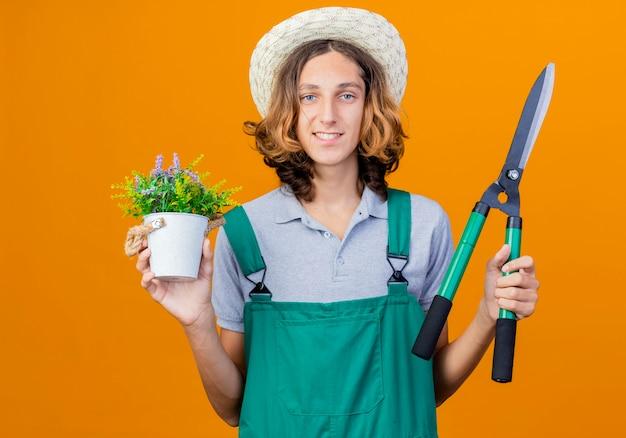 Jovem jardineiro vestindo macacão e chapéu segurando um cortador de cerca viva e um vaso de plantas