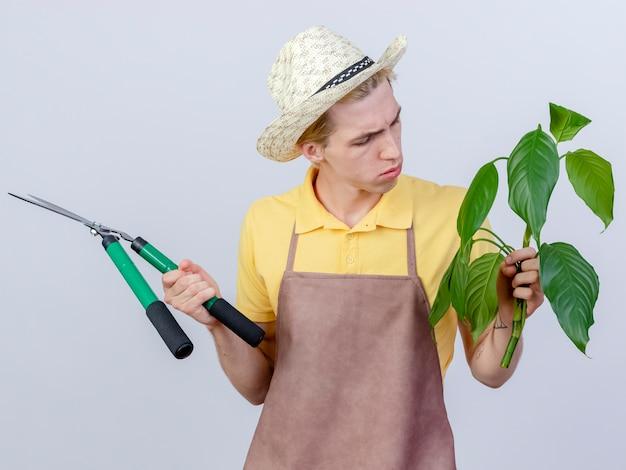 Jovem jardineiro vestindo macacão e chapéu segurando um cortador de cerca viva e uma planta olhando para ela intrigado