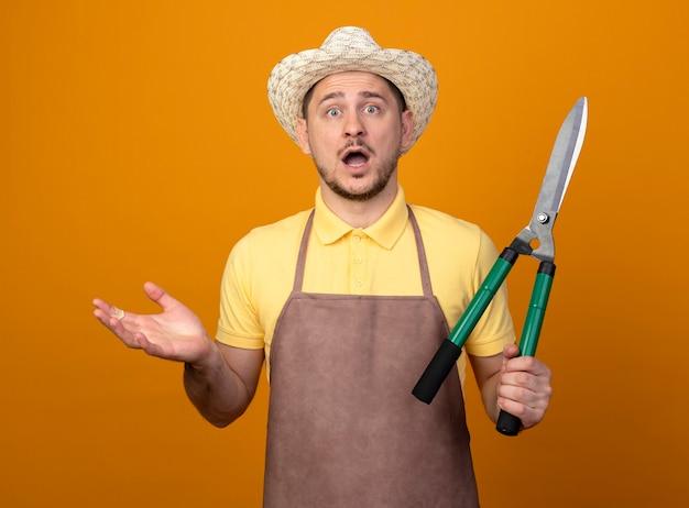 Jovem jardineiro vestindo macacão e chapéu segurando um cortador de cerca viva olhando para a frente espantado e surpreso em pé sobre a parede laranja