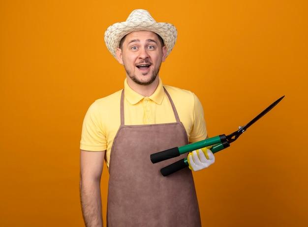 Jovem jardineiro vestindo macacão e chapéu segurando um cortador de cerca viva olhando para a frente feliz e surpreso em pé sobre a parede laranja