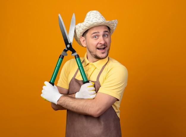 Jovem jardineiro vestindo macacão e chapéu segurando um cortador de cerca-viva olhando para a frente sorrindo com uma cara feliz em pé sobre a parede laranja
