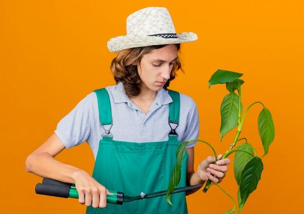 Jovem jardineiro vestindo macacão e chapéu segurando um corte de planta com uma tesoura de sebe