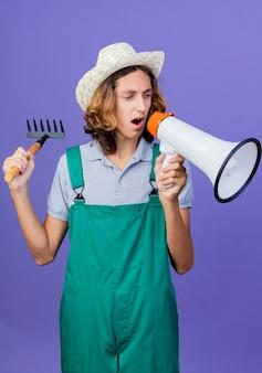 Jovem jardineiro vestindo macacão e chapéu segurando um mini ancinho gritando