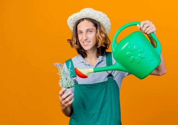 Jovem jardineiro vestindo macacão e chapéu segurando um regador e um vaso de planta Foto gratuita
