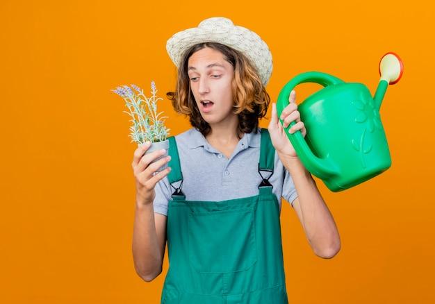 Jovem jardineiro vestindo macacão e chapéu segurando um regador e um vaso de planta