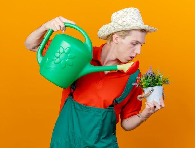 Jovem jardineiro vestindo macacão e chapéu segurando um regador