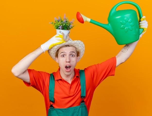 Jovem jardineiro vestindo macacão e chapéu segurando um regador Foto gratuita