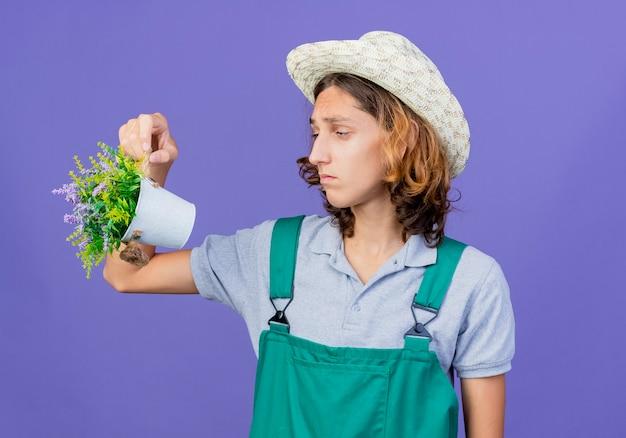 Jovem jardineiro vestindo macacão e chapéu segurando um vaso de planta olhando triste