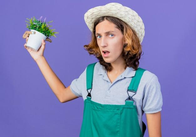 Jovem jardineiro vestindo macacão e chapéu segurando um vaso de plantas com raiva