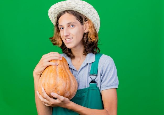 Jovem jardineiro vestindo macacão e chapéu segurando uma abóbora e sorrindo com uma cara feliz