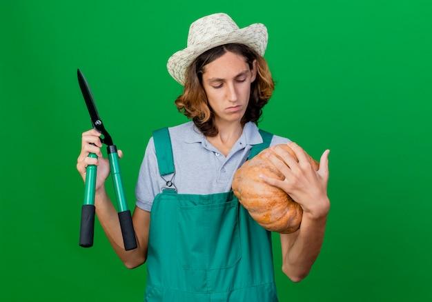 Jovem jardineiro vestindo macacão e chapéu segurando uma abóbora e um cortador de cerca viva