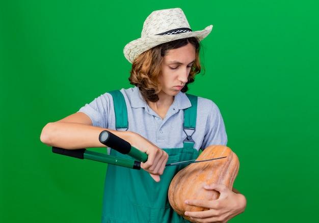 Jovem jardineiro vestindo macacão e chapéu segurando uma abóbora