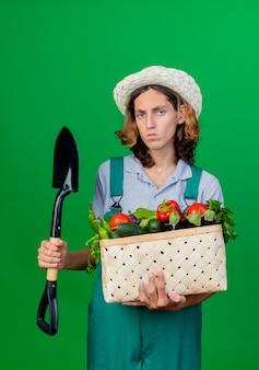 Jovem jardineiro vestindo macacão e chapéu segurando uma caixa cheia de vegetais frescos