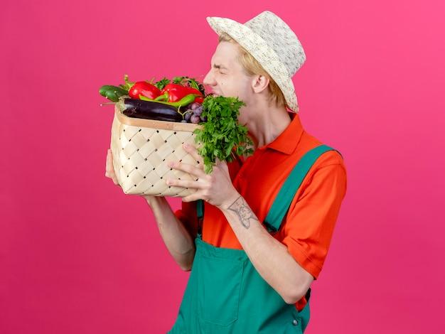 Jovem jardineiro vestindo macacão e chapéu segurando uma caixa cheia de vegetais