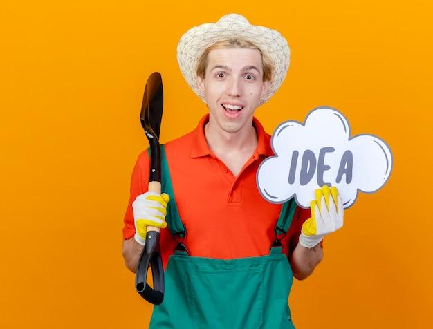 Jovem jardineiro vestindo macacão e chapéu segurando uma pá e um cartaz de balão