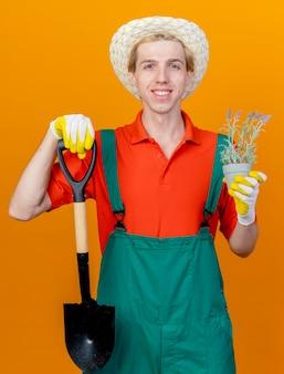 Jovem jardineiro vestindo macacão e chapéu segurando uma pá e um vaso de plantas