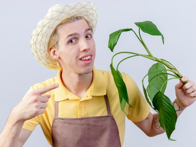 Jovem jardineiro vestindo macacão e chapéu segurando uma planta apontando com o dedo indicador para ela, sorrindo com uma cara feliz em pé sobre um fundo branco