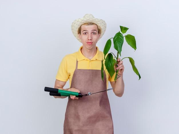 Jovem jardineiro vestindo macacão e chapéu segurando uma planta e um cortador de cerca viva com um sorriso no rosto