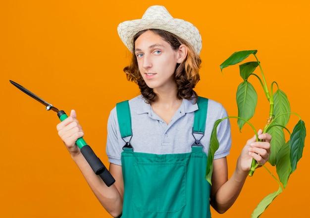 Jovem jardineiro vestindo macacão e chapéu segurando uma planta e um cortador de cerca viva