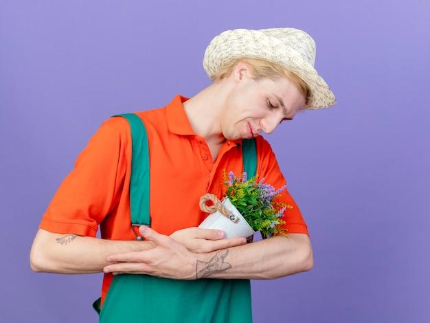 Jovem jardineiro vestindo macacão e chapéu segurando uma planta em um vaso como se fosse um bebê