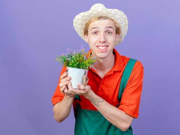 Jovem jardineiro vestindo macacão e chapéu segurando uma planta em um vaso, olhando para a câmera, sorrindo com uma cara feliz em pé sobre um fundo roxo