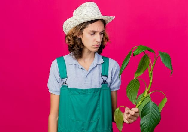 Jovem jardineiro vestindo macacão e chapéu segurando uma planta olhando para ela com uma cara séria