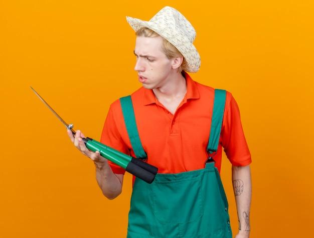 Jovem jardineiro vestindo macacão e chapéu segurando uma tesoura de cerca-viva olhando para uma tesoura com cara séria em pé sobre um fundo laranja