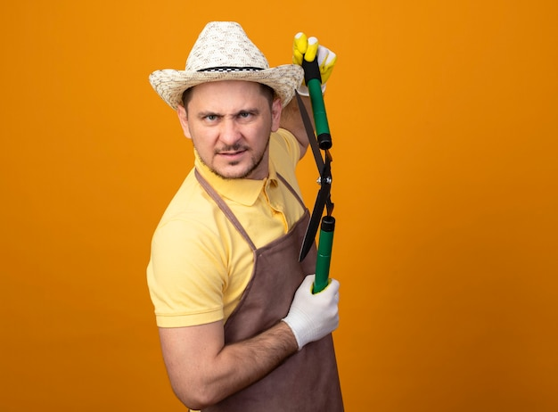 Jovem jardineiro vestindo macacão e chapéu segurando uma tesoura de cortar sebes com cara de raiva