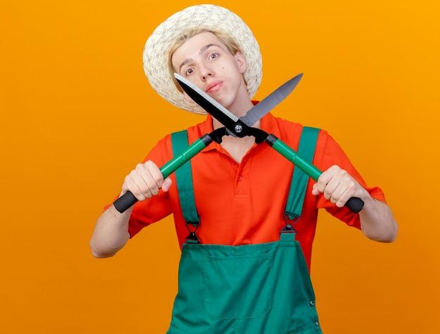 Jovem jardineiro vestindo macacão e chapéu segurando uma tesoura de cortar sebes com cara séria