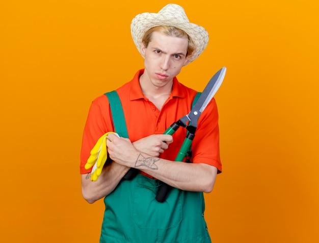Jovem jardineiro vestindo macacão e chapéu segurando uma tesoura de sebe e luvas de borracha, olhando para a câmera com uma cara séria em pé sobre um fundo laranja