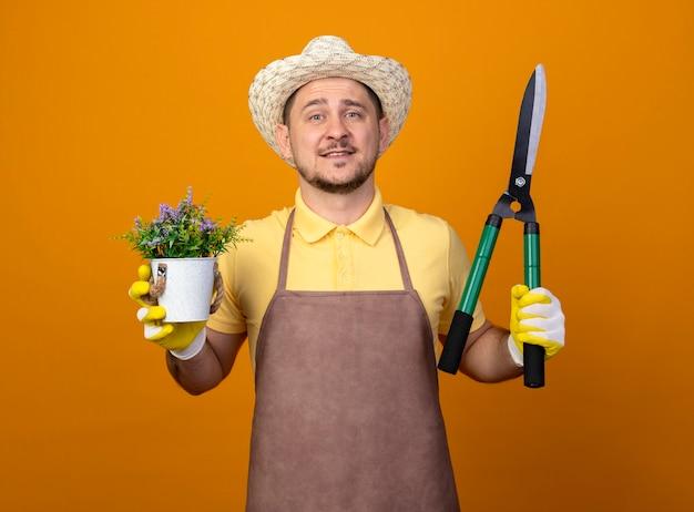 Jovem jardineiro vestindo macacão e chapéu segurando uma tesoura de sebes e um vaso de plantas olhando para a frente com uma cara feliz sorrindo em pé sobre a parede laranja