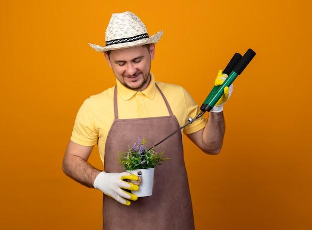 Jovem jardineiro vestindo macacão e chapéu segurando uma tesoura de sebes e um vaso de plantas olhando para ela com um sorriso no rosto em pé sobre a parede laranja