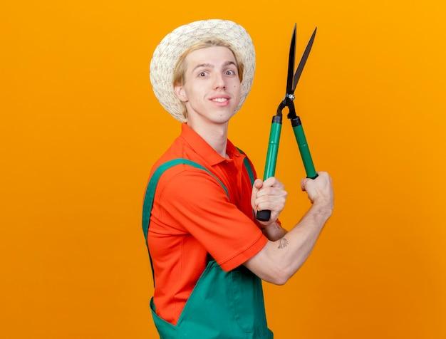 Jovem jardineiro vestindo macacão e chapéu segurando uma tesoura de sebes, olhando para a câmera com um sorriso no rosto em pé sobre um fundo laranja