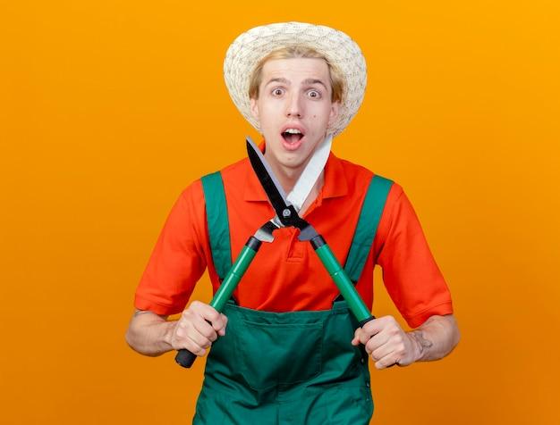 Jovem jardineiro vestindo macacão e chapéu segurando uma tesoura de sebes, olhando para a câmera, sendo surpreendido e maravilhado em pé sobre um fundo laranja