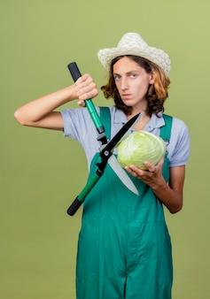 Jovem jardineiro vestindo macacão e chapéu segurando uma tesoura para sebes
