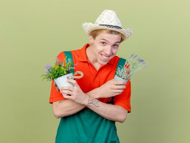 Jovem jardineiro vestindo macacão e chapéu segurando vasos de plantas olhando para a câmera, sorrindo e piscando feliz e positivo em pé sobre um fundo claro